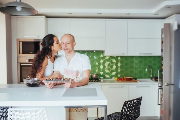 Beau jeune couple dessiné souriant en cuisinant dans la cuisine à la maison. Photo Premium