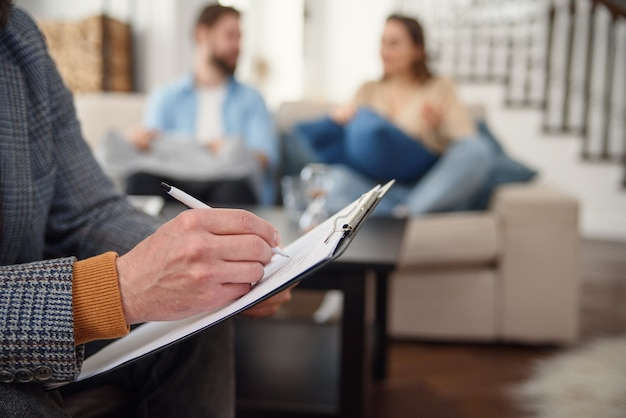 Beau Jeune Couple Est Assis Sur Un Canapé Et Parle Au Psychologue Pendant Que Le Médecin Prend Des Notes Photo Premium