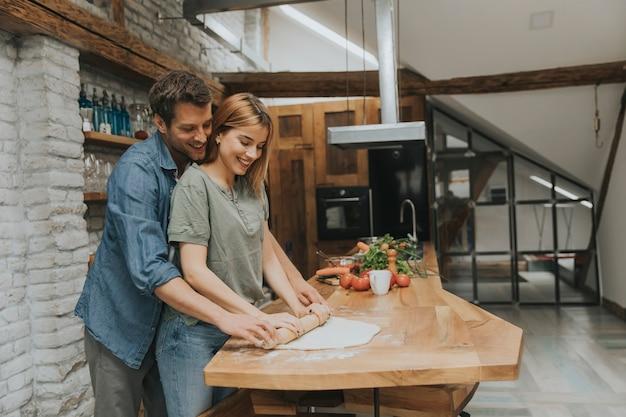 Beau jeune couple gai, préparer le dîner ensemble et s'amuser à la cuisine rustique Photo Premium