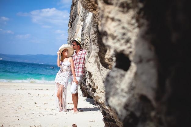 Beau jeune couple heureux sur la plage, contre la mer et les montagnes. Photo Premium