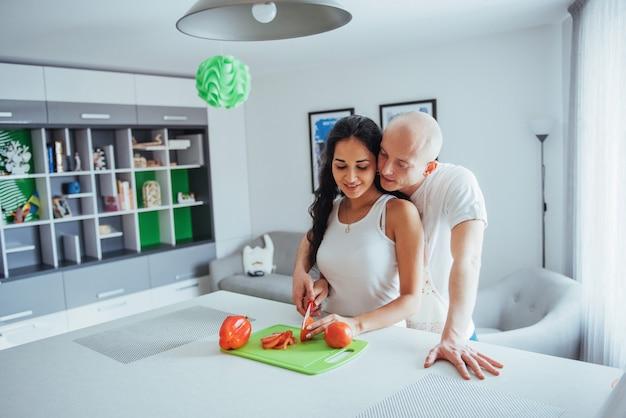Beau Jeune Couple Moudre Les Légumes Ensemble Dans La Cuisine. Photo Premium