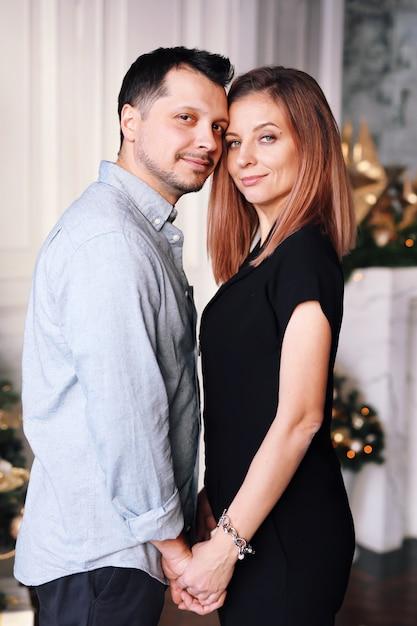 Beau jeune couple à noël. une jeune femme et un homme sourient et s'amusent ensemble. Photo Premium