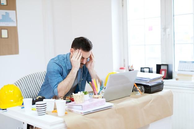 Beau Jeune Designer Moderne Fatigué Faisant Une Pause Du Travail Avec La Tête De Massage Et La Fermeture Des Yeux Dans Le Bureau Lumineux. Photo Premium
