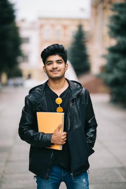 Beau Jeune étudiant Indien Homme Tenant Des Cahiers En Se Tenant Debout Dans La Rue Photo gratuit