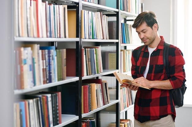 Beau Jeune étudiant Lisant L'un Des Livres De La Bibliothèque Du Collège Tout En Choisissant La Littérature éducative Photo Premium