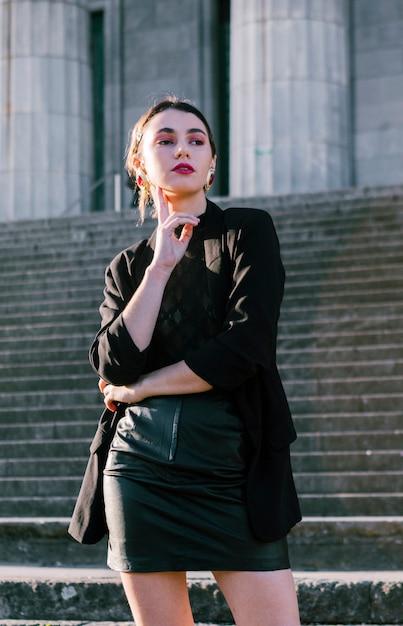 Beau, jeune femme, à, main, menton, debout, devant, escaliers Photo gratuit