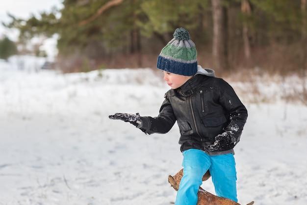 Beau jeune garçon dans la forêt d'hiver. Photo Premium