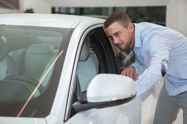 Beau jeune homme, acheter une nouvelle voiture au salon de la concession Photo Premium