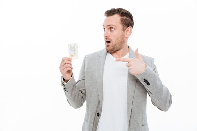Beau jeune homme d'affaires choqué pointant tout en maintenant la carte de crédit. Photo gratuit