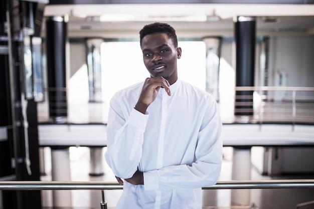 Beau Jeune Homme D'affaires à Lunettes Pense Tout En Se Tenant Dans Le Hall Du Bureau Photo gratuit