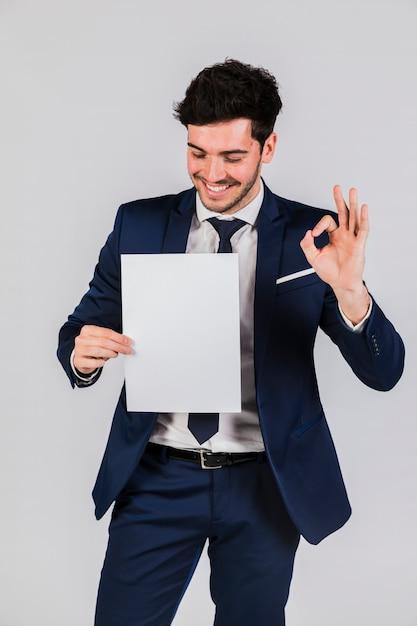 Beau, jeune homme d'affaires, tenant livre blanc, dans main, montrer signe ok, contre, gris, toile de fond Photo gratuit