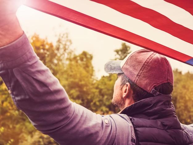 Beau jeune homme agitant un drapeau américain Photo Premium