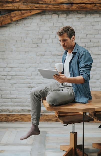 Beau jeune homme à l'aide de tablette numérique et buvant du café tout en étant assis dans la salle rustique Photo Premium
