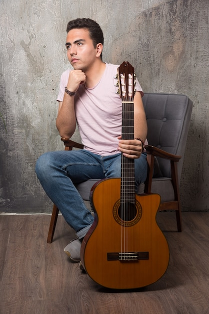 Beau Jeune Homme Assis Sur La Chaise Tout En Tenant La Guitare. Photo gratuit