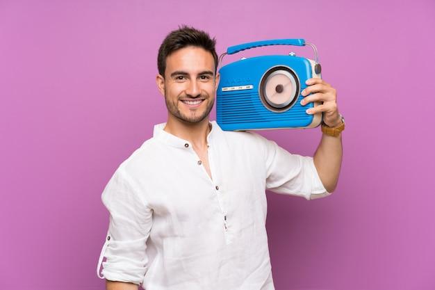 Beau jeune homme au mur violet tenant une radio Photo Premium