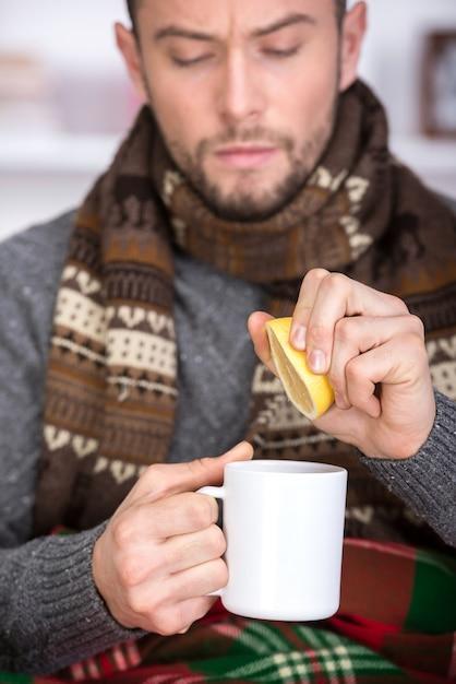Beau jeune homme boit du thé au citron. Photo Premium
