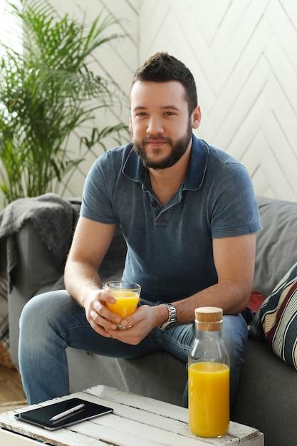 Beau Jeune Homme Buvant Du Jus D'orange à La Maison Photo gratuit