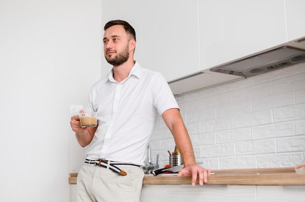 Beau jeune homme avec café à la main Photo gratuit
