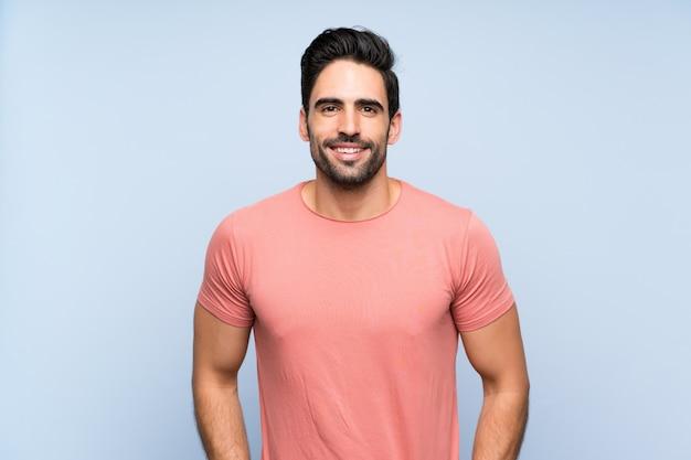 Beau jeune homme en chemise rose sur le mur bleu isolé en riant Photo Premium