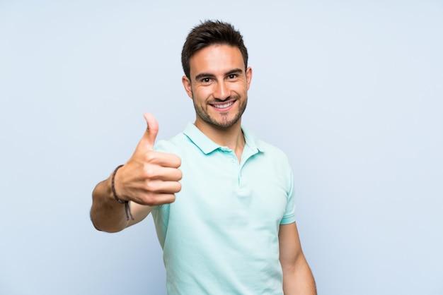 Beau jeune homme isolé avec un pouce levé parce qu'il s'est passé quelque chose de bien Photo Premium