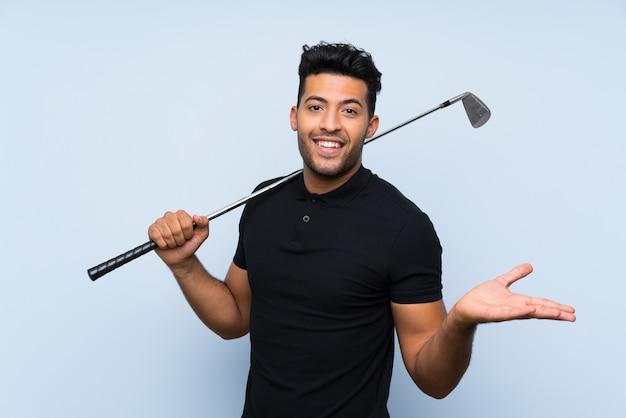 Beau jeune homme jouant au golf sur un mur bleu isolé avec une expression faciale choquée Photo Premium
