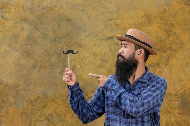Beau jeune homme avec une longue barbe avec une moustache de jouet Photo gratuit