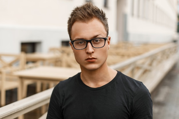 Beau Jeune Homme Avec Des Lunettes Dans Une Chemise Noire Debout Dans La Rue. Photo Premium