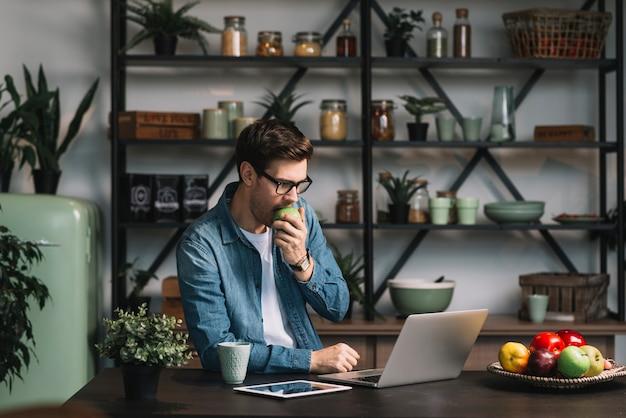 Beau jeune homme mange des pommes en regardant une tablette numérique dans la cuisine Photo gratuit