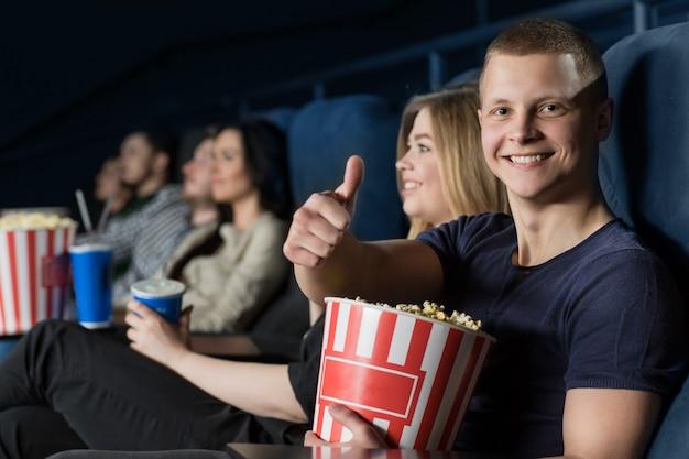 Beau jeune homme montrant les pouces en regardant un film au cinéma Photo Premium