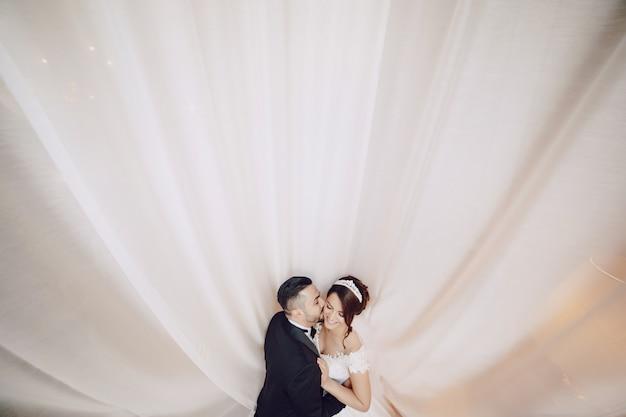 Un beau jeune homme portant un costume noir debout avec sa mariée Photo gratuit