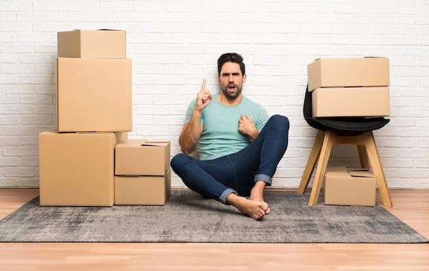 Beau jeune homme se déplaçant dans la nouvelle maison parmi les boîtes avec une expression faciale surprise Photo Premium