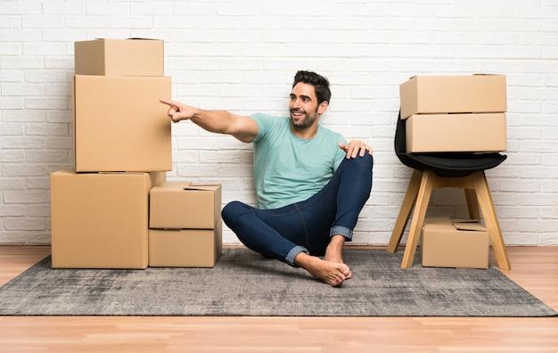 Beau jeune homme se déplaçant dans la nouvelle maison parmi les boîtes pointant le doigt sur le côté Photo Premium
