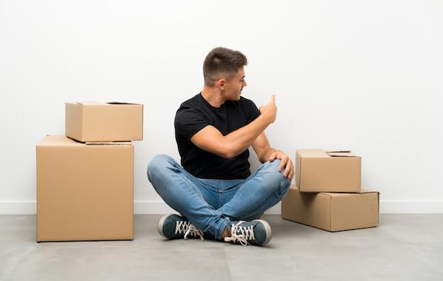 Beau jeune homme se déplaçant dans la nouvelle maison parmi les boîtes pointant vers l'arrière avec l'index Photo Premium