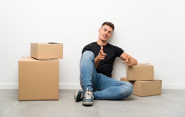 Beau jeune homme se déplaçant dans la nouvelle maison parmi les boîtes pointe le doigt vers vous Photo Premium