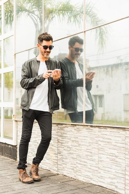 Beau jeune homme se penchant sur le mur de verre à l'aide de smartphone Photo gratuit