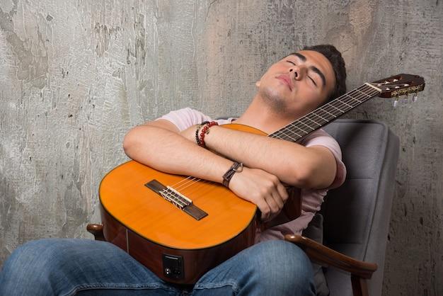 Beau Jeune Homme Tenant La Guitare Et Dormant Sur La Chaise. Photo gratuit
