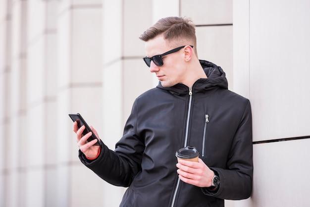 Beau jeune homme tenant une tasse de café à emporter à l'aide de smartphone Photo gratuit