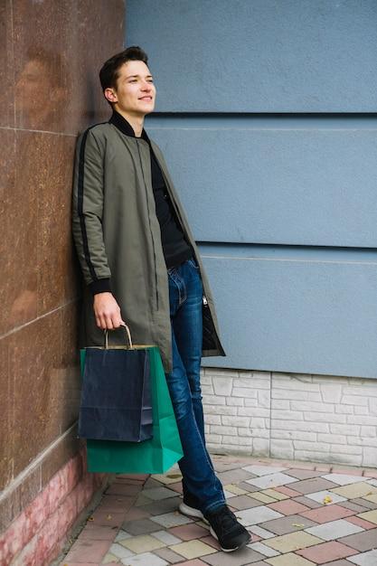 Beau, jeune homme, tenue, coloré, sacs, pencher mur, regarder loin Photo gratuit