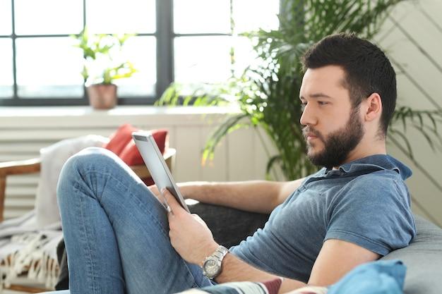 Beau Jeune Homme Utilisant Une Tablette Numérique Ou Un Ebook Photo gratuit