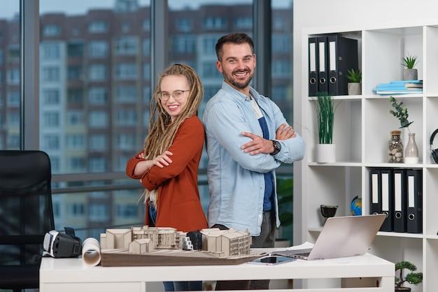 Beau Jeune Ingénieur Professionnel Se Tient Dos à Dos Avec Une Jolie Collègue Avec Des Dreadlocks Au Bureau D'études. Photo Premium