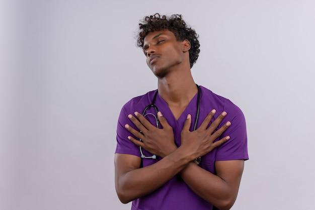 Un Beau Jeune Médecin à La Peau Foncée Réfléchie Avec Des Cheveux Bouclés Portant L'uniforme Violet Avec Stéthoscope Tenant Les Mains Sur Sa Poitrine Photo gratuit