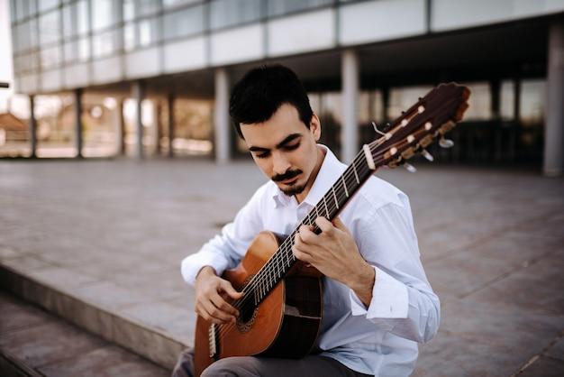 Beau jeune musicien jouant de la guitare classique dans la ville. Photo Premium