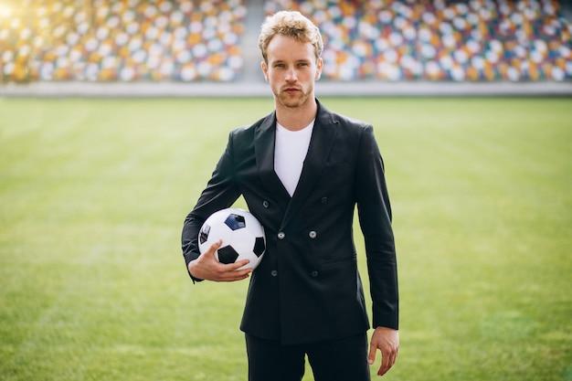 Beau joueur de football au stade en costume d'affaires Photo gratuit