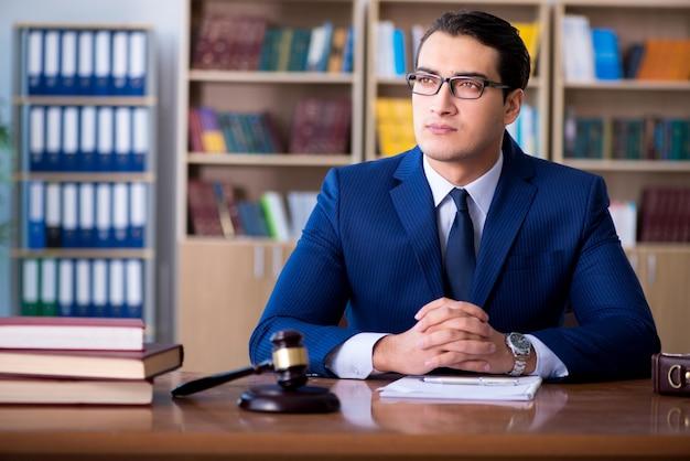Beau juge avec marteau assis dans la salle d'audience Photo Premium