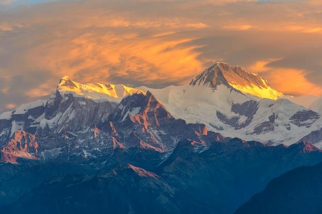 Beau lever de soleil nuageux dans les montagnes avec la crête de neige Photo Premium