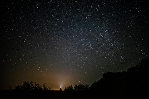 Beau long plan d'un homme assis sous le ciel Photo gratuit