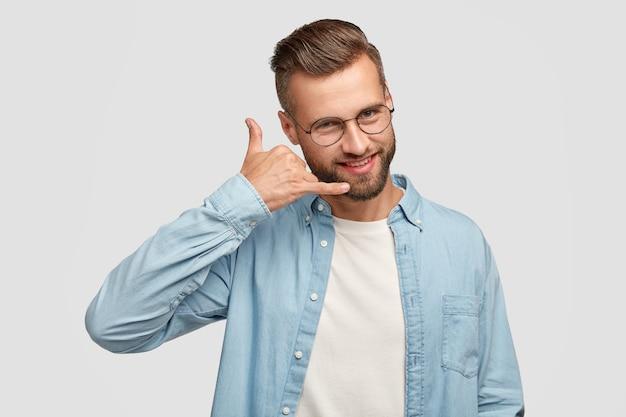 Un Beau Mâle Positif Fait Un Geste Téléphonique, Fait Semblant De Parler Au Téléphone Intelligent, A Une Expression Joyeuse, Vêtu D'une Chemise à La Mode, Isolé Sur Un Mur Blanc. Concept De Personnes Et De Communication Photo gratuit