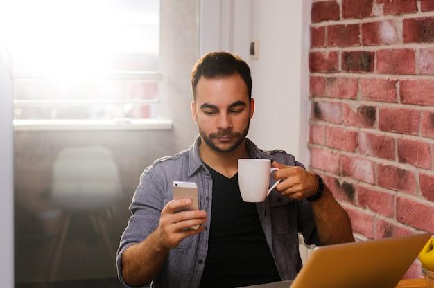 Beau mec buvant un café tout en regardant Photo Premium