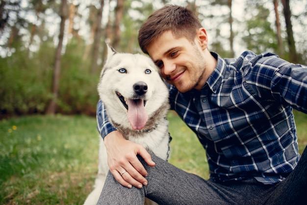 Beau mec dans un parc d'été avec un chien Photo gratuit