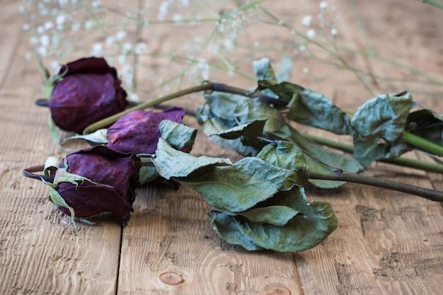 Beau millésime roses fanées sur un fond rustique. Photo Premium